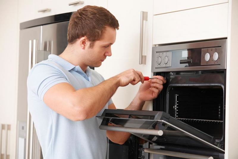 Licensed service provider fixing an oven covered by a home warranty company