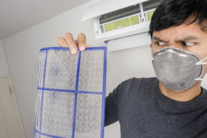 Man cleaning dirty air conditioner filter