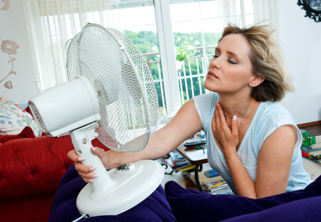 Woman using fan to cool because AC broken