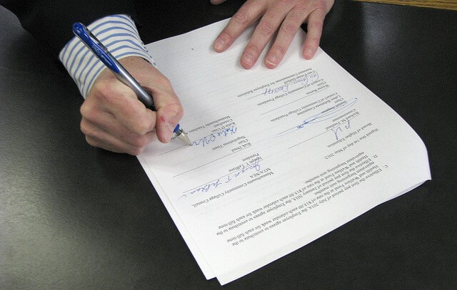 man signing home warranty documents