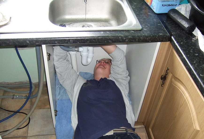 woman fixing sink at home