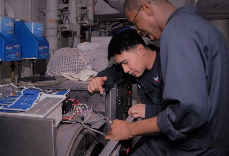 men repairing washing machine