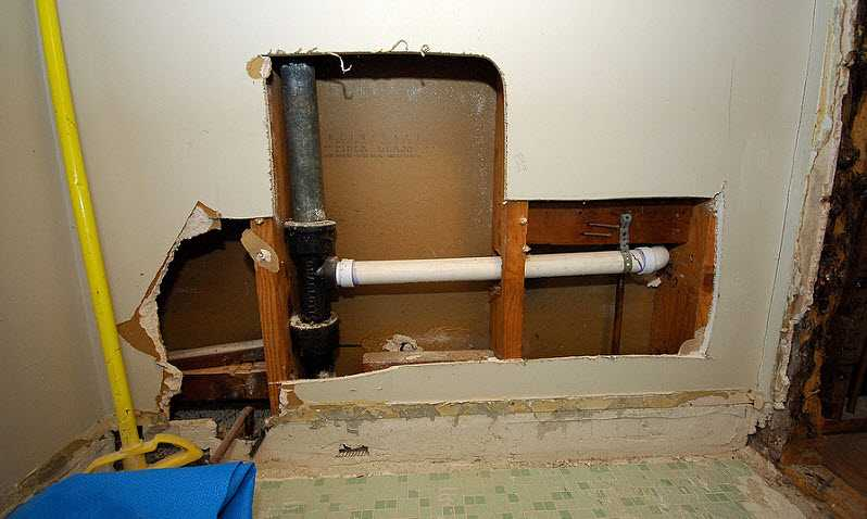 wall cutout of bad plumbing in house